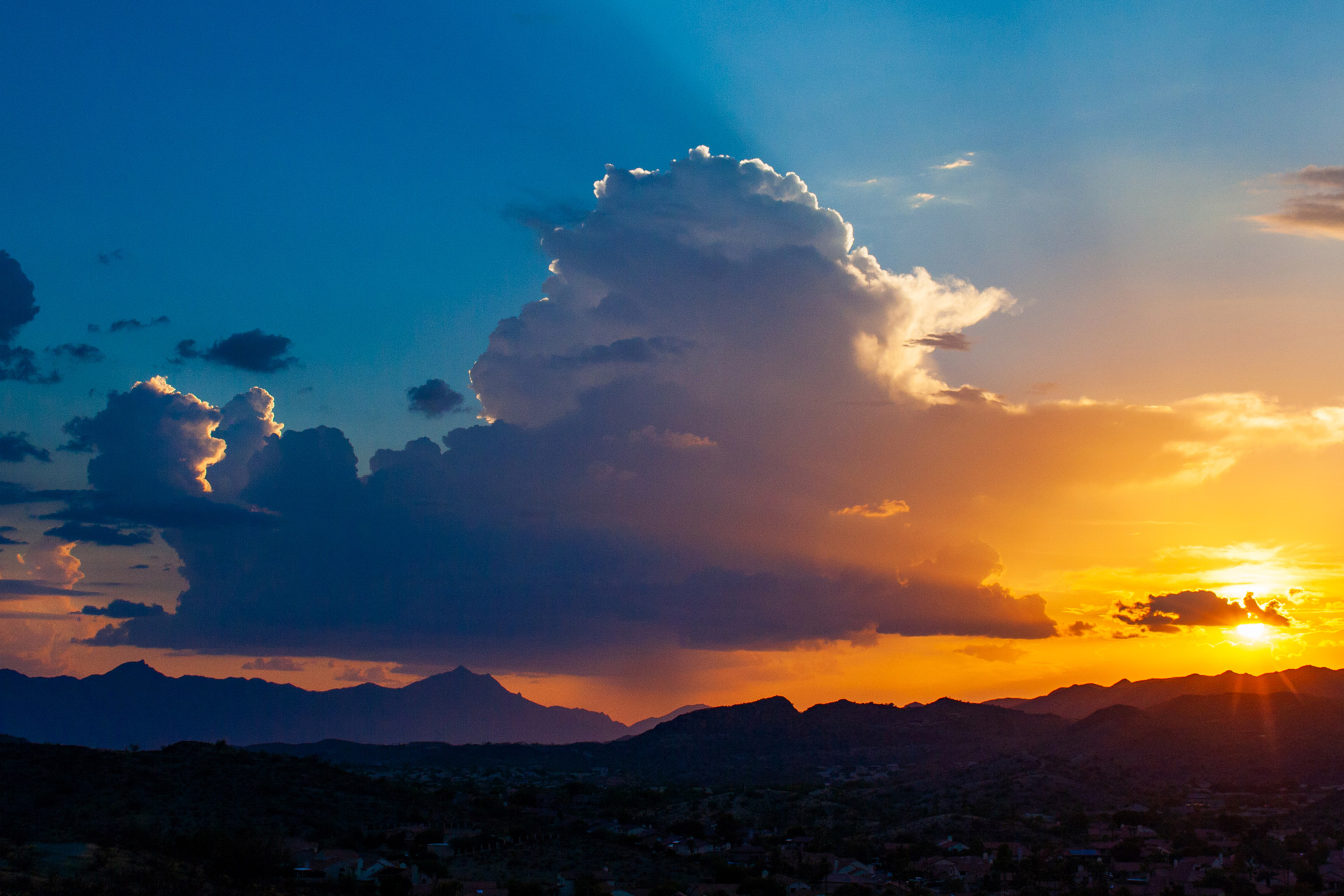 A thunderstorm to the west of Phoenix is illuminated by the setting sun